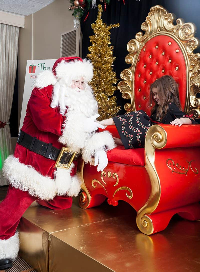 A little girl sits in Santa's chair at the Swissotel with Santa.