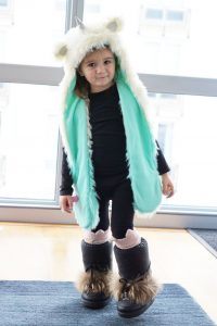A toddler wears a fur hat with fur boots in Chicago.