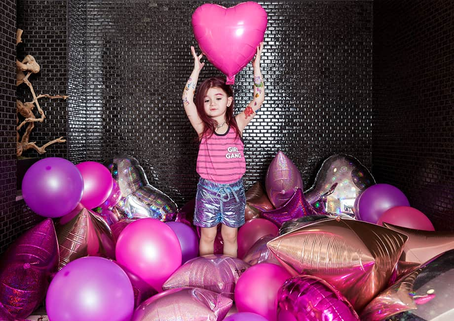 A toddler stands in a room filled with pink balloons.