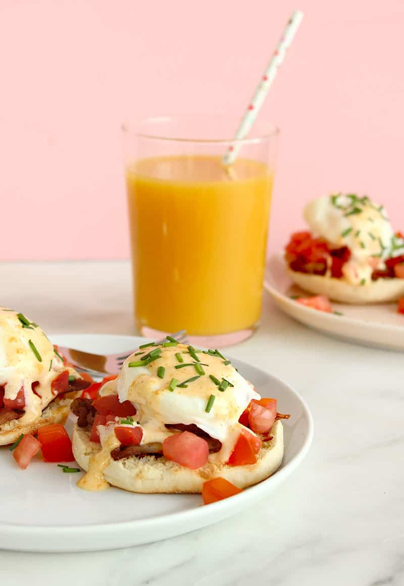 A BLT Eggs Benedict with Faux Hollandaise sits next to a glass of orange juice.