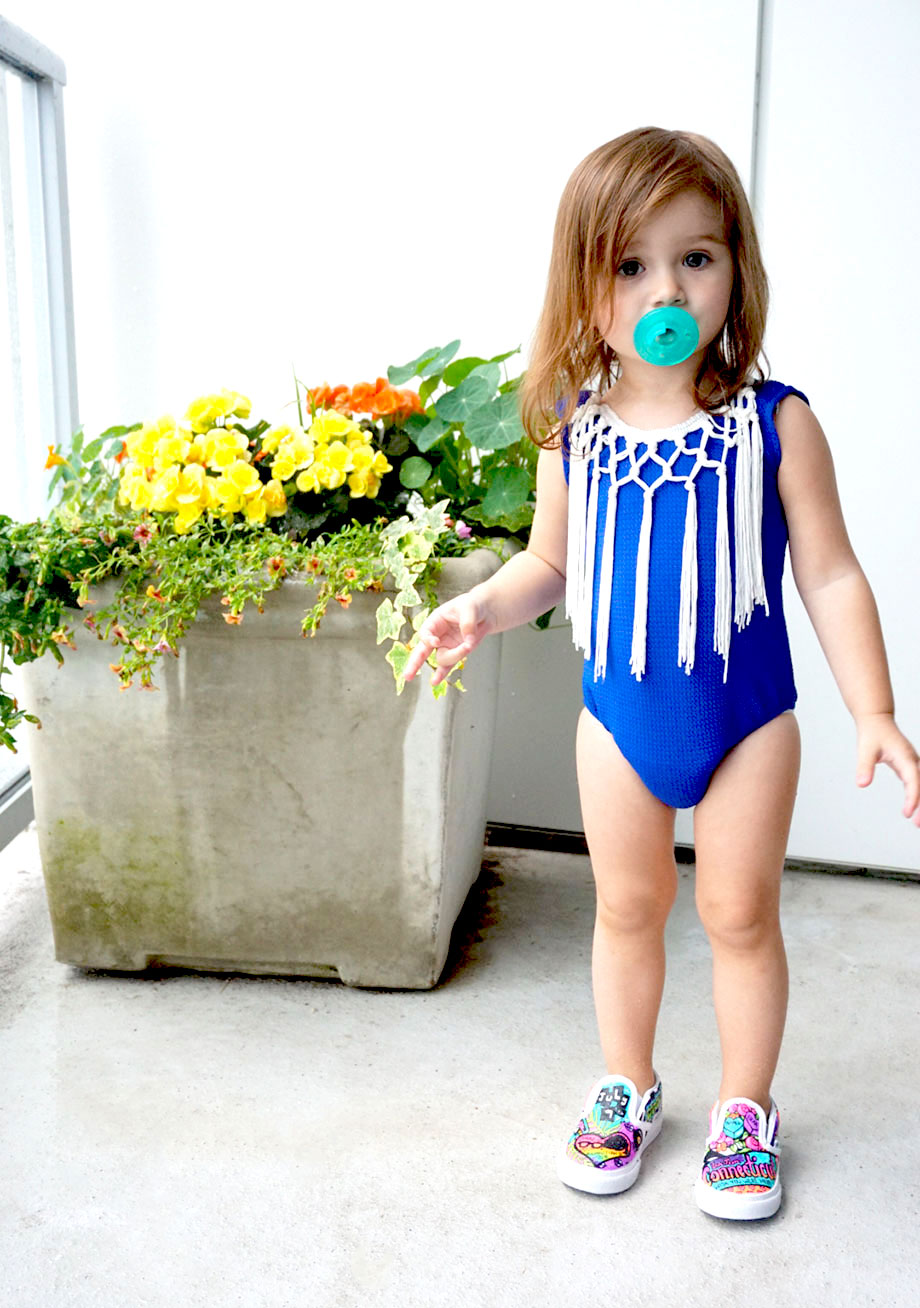 A toddler stands in a blue bathing suit with a pacifier.