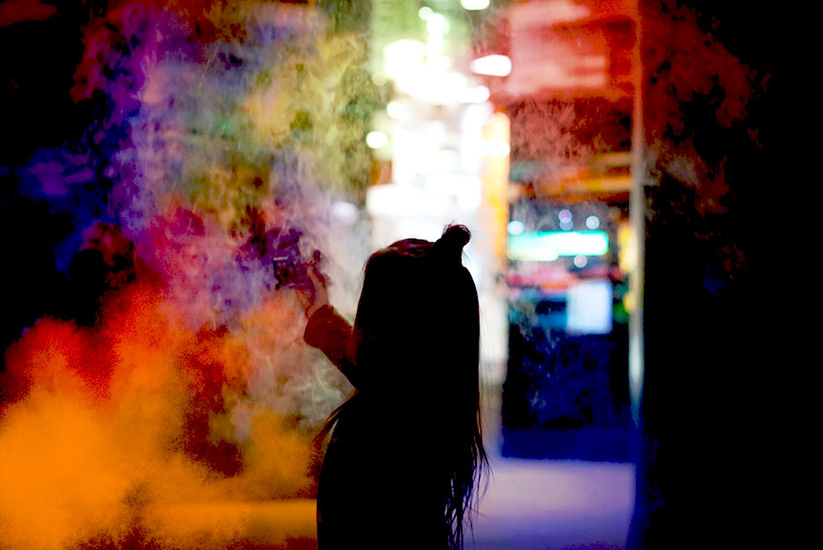 A toddler stands in front of a colorful wall of smoke at the Museum of Science and Industry.